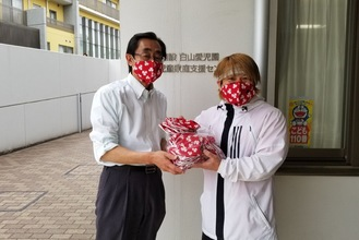 白山愛児園でマスクを手渡す田村代表(右)=本人提供