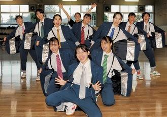 衣装を着てポーズをとるメンバーと蓑毛教諭(後方中央)=24日、同校