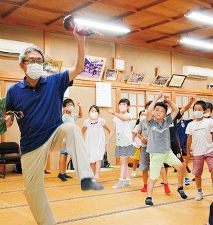児童に踊りを指導する金子会長(左)=11日