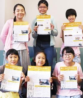 完成した新聞を手に、笑顔をみせるミニカワサキのメンバー