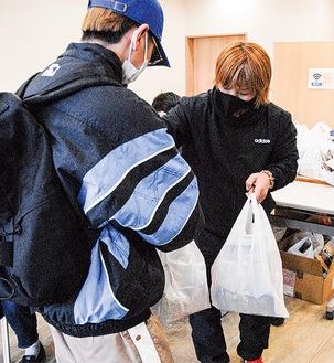 学生に袋を渡す協力メンバー