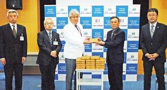 石橋会長から寄贈品を受け取る長島病院長(中央)