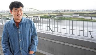 ドラマにも登場した多摩川と小田急線、多摩水道橋の景色を前に、思いを語る中川龍太郎監督=5月19日