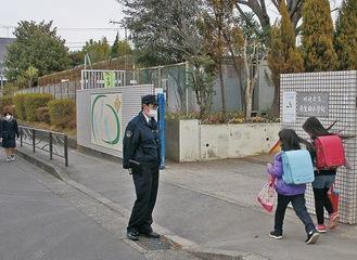 小学校の校門前で見守る多摩署員=同署提供