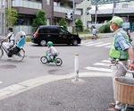 交差点付近に立つ町会役員(昨年5月28日)