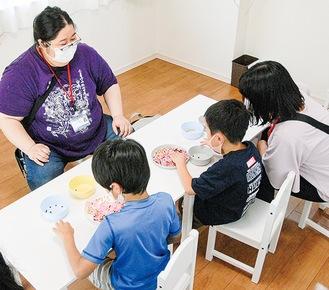 ゲームを教える田中さん(左)