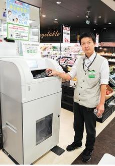 ボトル回収機を操作する由井店長