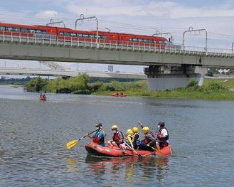 小田急線高架下付近をラフティングボートで巡る参加者