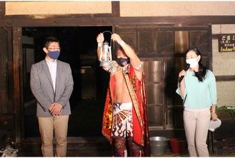 多摩区採火者の和秀俊さん(左)から種火入りのランタンを受け取った、市採火式の区代表者・田村和宏さん(中央)=区提供
