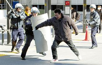 刃物を持った犯人役を囲む警察官