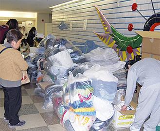 支援物資から必要品を探す被災者ら