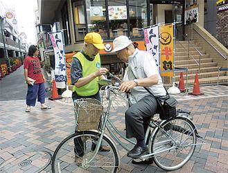 元住吉駅前で啓発物を配る参加者