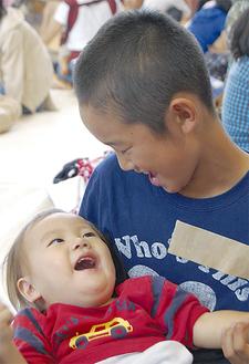 笑顔で触れ合う赤ちゃんと児童