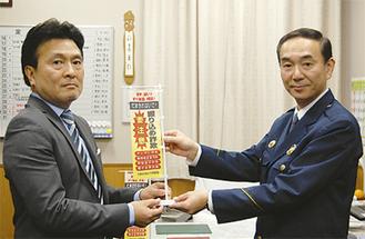 旗を受け取る中村会長(左)
