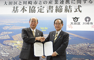 協定書を手に握手する阿部市長(右)と松原区長