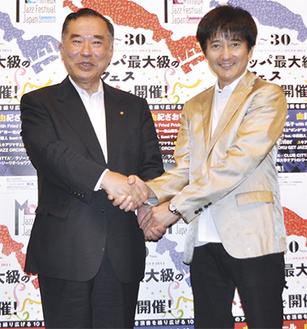 握手を交わす山田委員長(左)と本田さん
