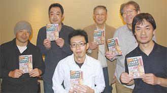 記念冊子を手にする組合メンバー