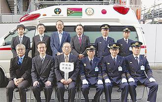 寄贈する救急車を背に整列するRCメンバーと市消防局員ら
