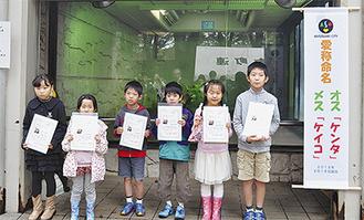 レッサーパンダ展示場の前で命名証を手にする児童