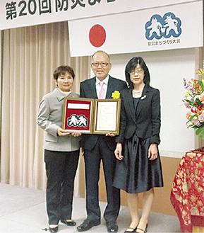 盾を手にする柳沢理事長(中央)