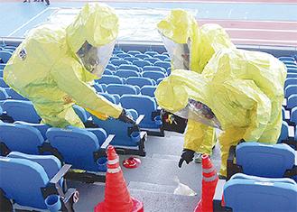 不審な袋を処理する消防隊員