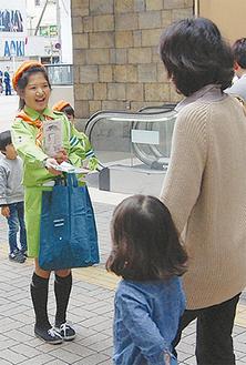 笑顔で啓発物を配る児童指導員