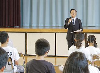 生徒を前に挨拶する清水会長