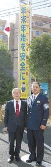 贈呈した懸垂幕と田中会長(左)、岩滿優署長