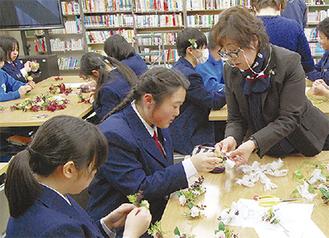 生徒に教える伊藤さん(右)