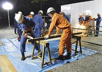 木材を切断する消防団員