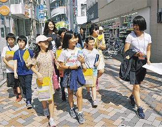 商店街を歩く児童と慶大生(右)