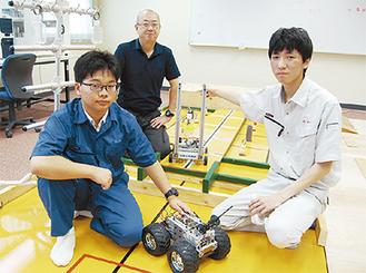 制作したロボットを手にする部員と、顧問の尾花教諭(中央)