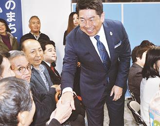 当選確実の一報を受け、支援者と握手を交わす福田氏=22日午後8時過ぎ