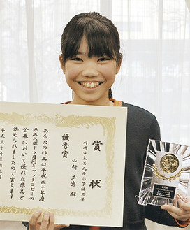 賞状と楯を手に笑顔をみせる山村さん