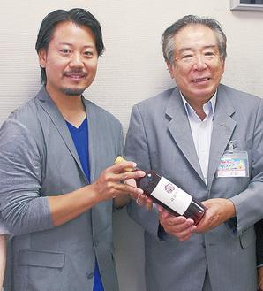 原組合長(右)にワインを手渡す山田代表(左)