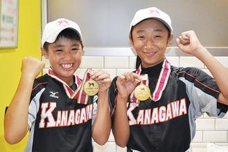 金メダルを手に笑顔をみせる八尾さん(右)と竹村さん(左)