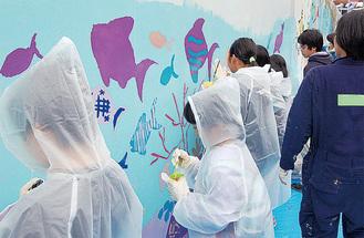 壁に絵を描く参加者