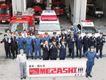 ロゴマークを掲げ雑誌の撮影。(中央左から)向坂区長、谷消防署長、則次警察署長