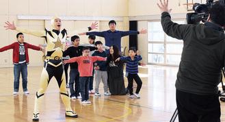 ストレッチマンゴールドと「ストレッチ体操」をする児童