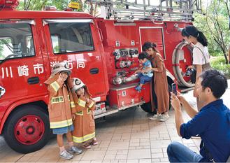 子ども用消防服を着て撮影する参加者ら