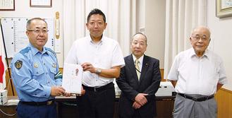 蒲山署長に目録を手渡す原会長、豊島さん、中田さん(右)