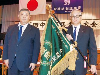 贈られた旗を手にする伊藤会長(右)と朝山会長