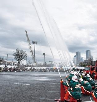 観客が見守る中、消防団員が一斉放水