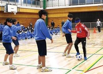 生徒のディフェンスをかわす丹羽選手(右)