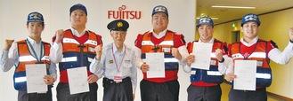 布施団長(左から3人目)から任命された富士通の安東純一さん、大久保さん、久下裕一郎さん、高口宏起さん、吉澤忠晃さん