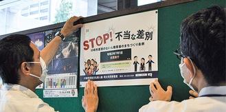 ポスターを掲示する市の職員