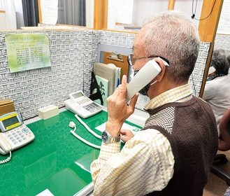 電話相談に応じる有田さん