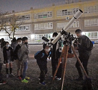 天体望遠鏡をのぞき込む児童ら