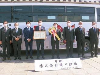 寄贈したバスと織戸社長(左から4人目)ら