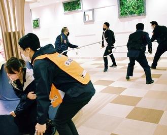 ケガ人役を救護するスタッフ(手前)と犯人役を取り押さえる警備員(奥)
